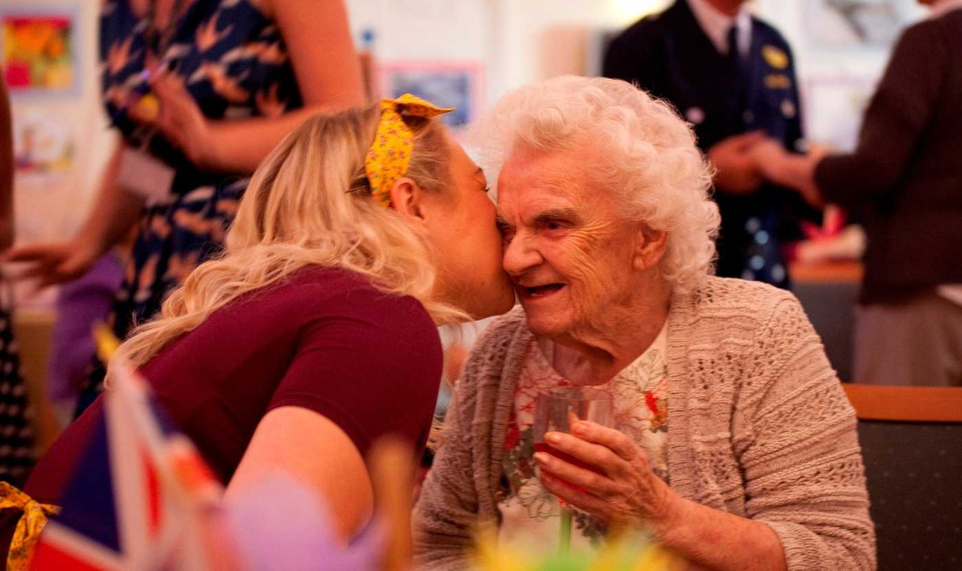 A younger woman kissing an elderly lady