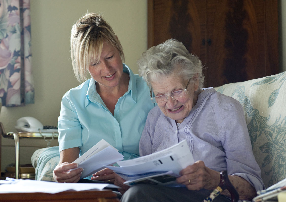 Home care worker opens post with customer as part of her personalised home care in Bristol