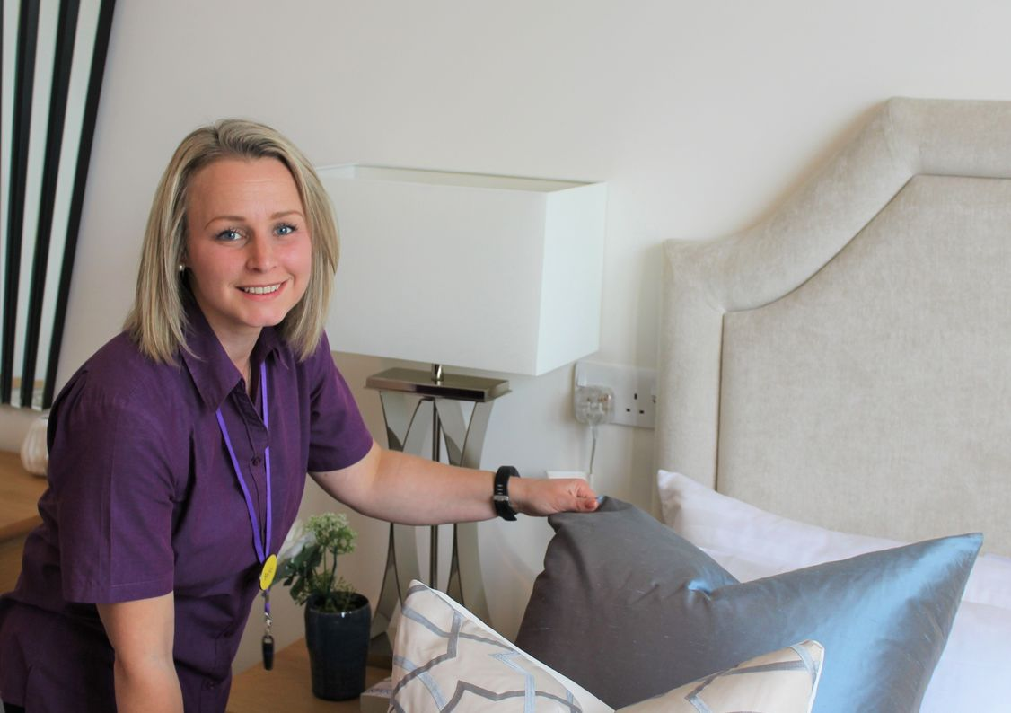 A member of St Monica Trust Care at Home makes a bed, part of the flexible service offering home care in Bristol