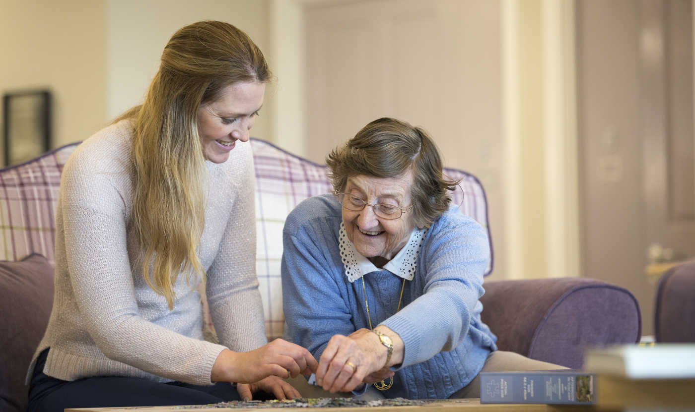 A residents plays dominoes while receiving respite care in Bristol