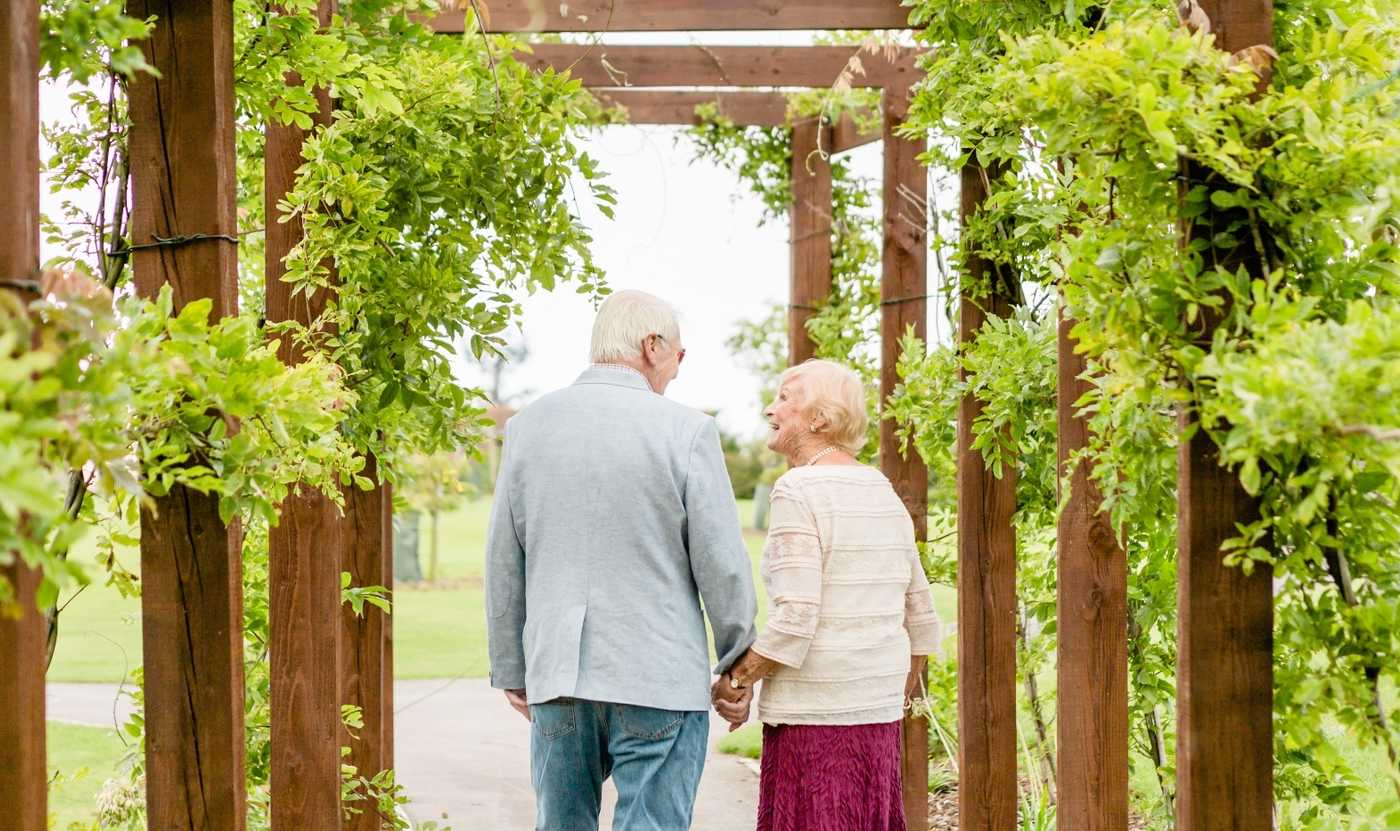 An elderly couple walk hand in hand through an arch and climbing plants