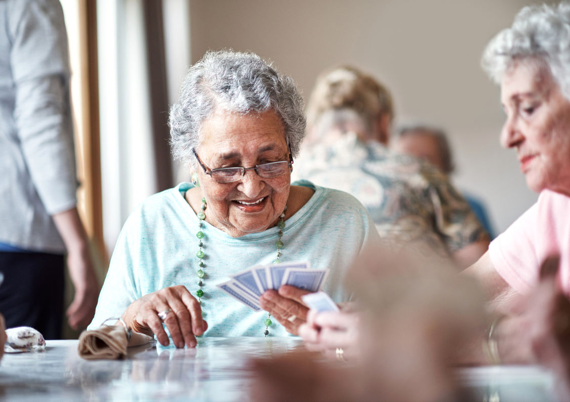 A lady plays cards during her stay for respite care in Bristol