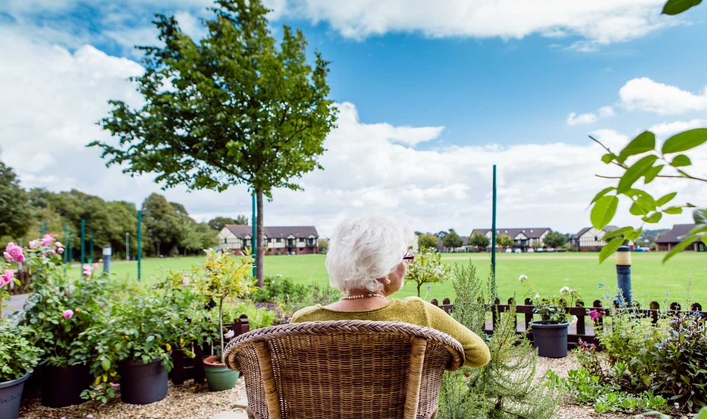 An elderly lady relaxes in a garden chair overlooking the cricket pitch at Westbury Fields Retirement Village