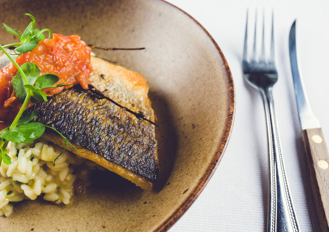 A beautiful fish dish on a plate with knife and fork