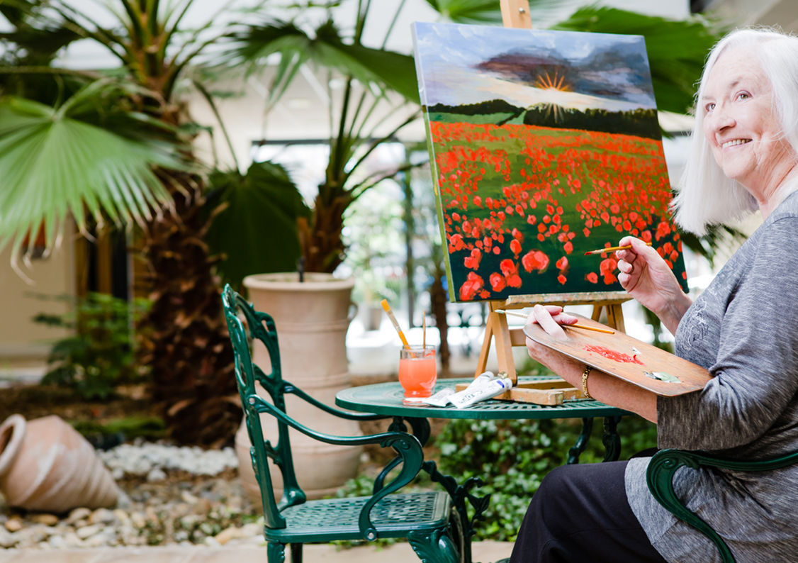 An elderly lady painting a picture