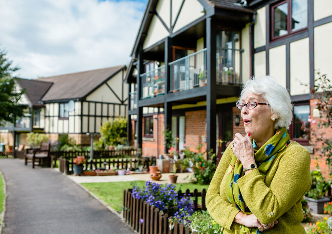 An elderly woman standing outside the house at Westbury Fields Retirement Village