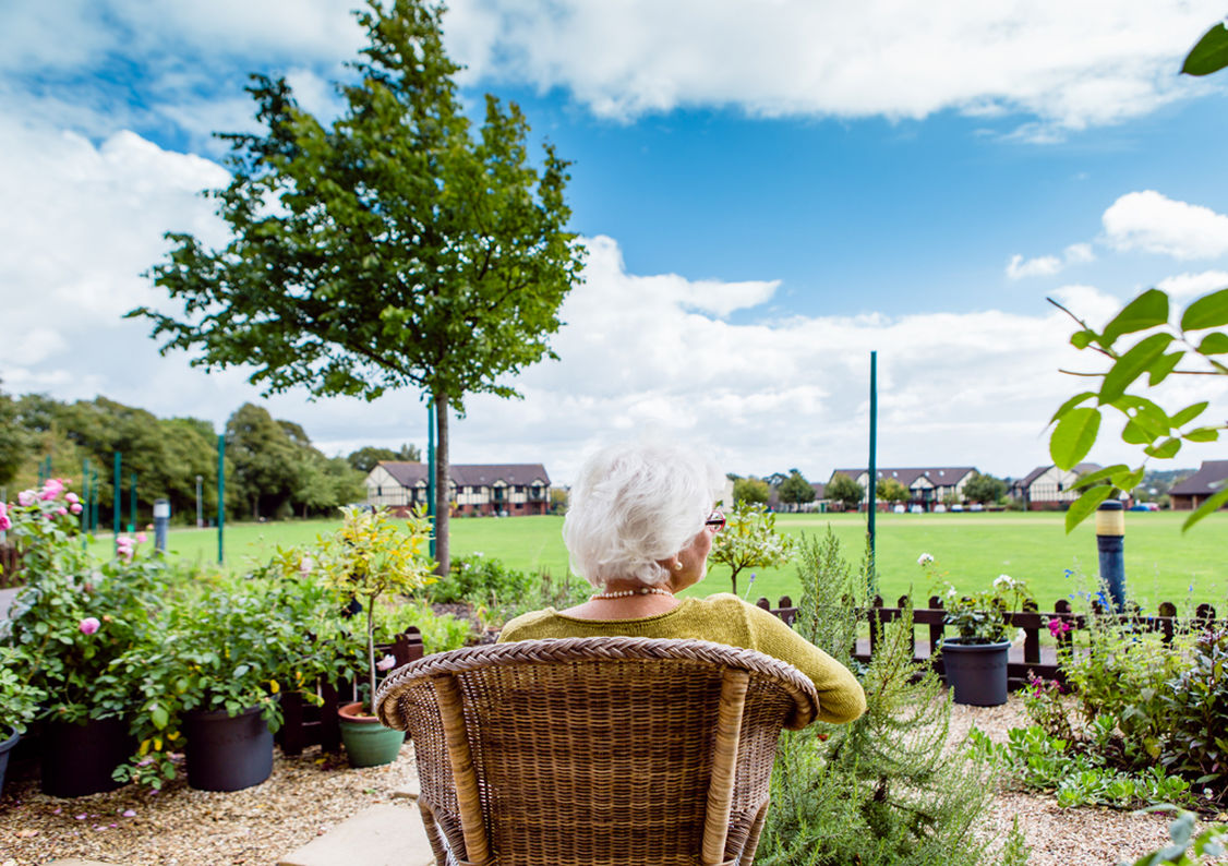 An elderly lady relaxes on a chair in her garden in Westbury Fields