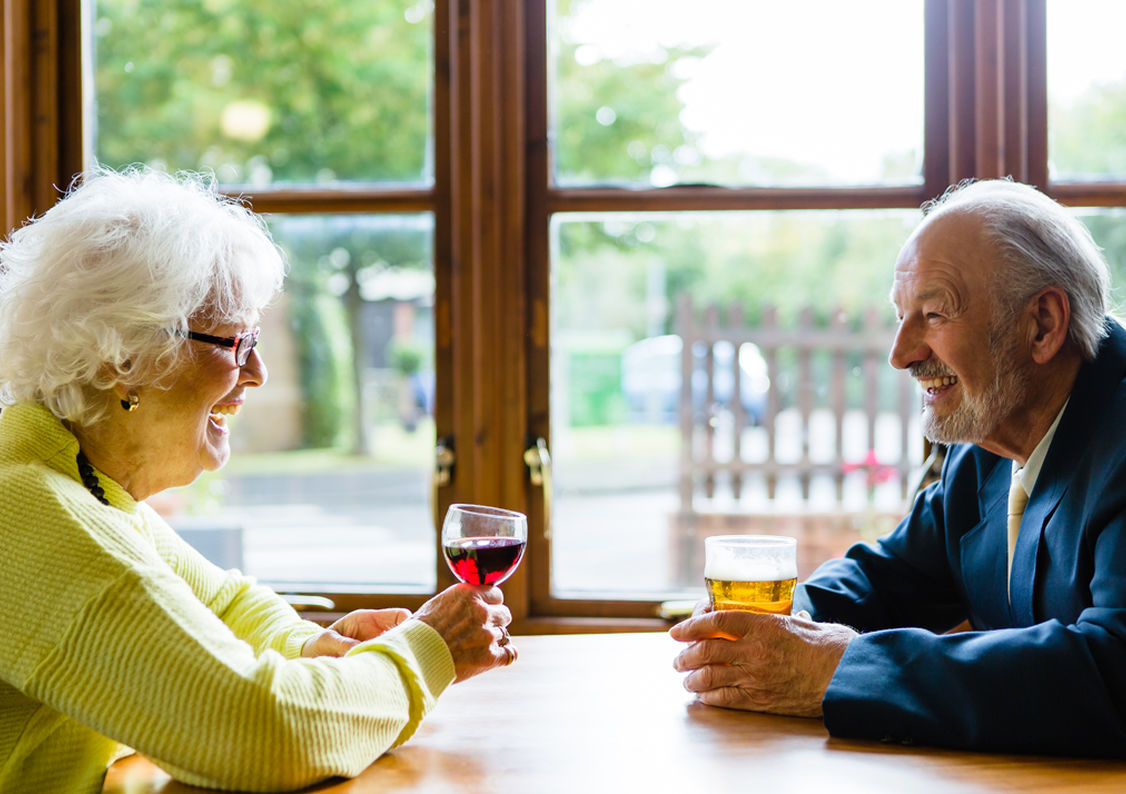 An elderly man and elderly lady sitting at a table having a drink together