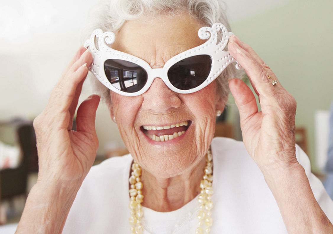 An elderly lady with a big smile wearing fancy sunglasses