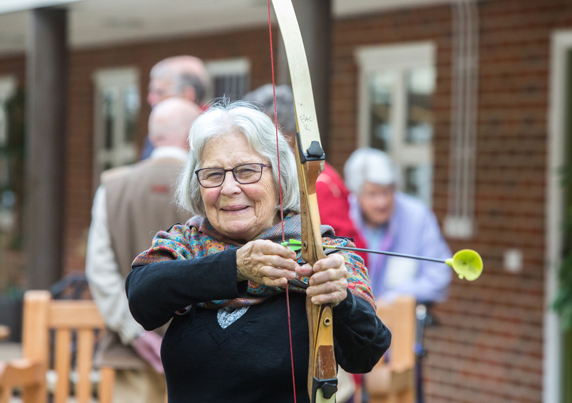 An elderly lady holding a bow and doing archery