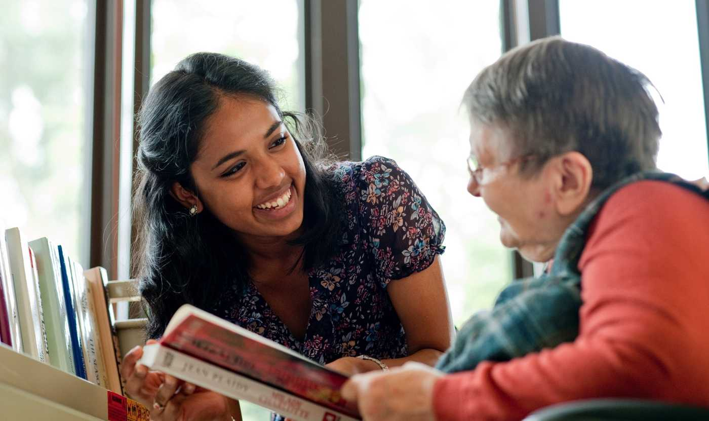 A volunteer spending time with an elderly lady