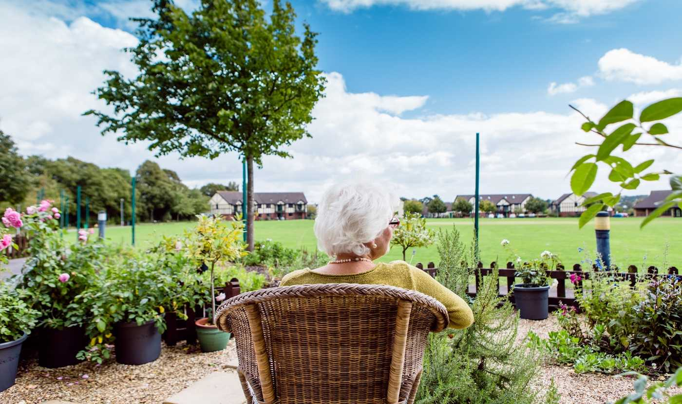 An elderly lady sat in a chair in her garden at Westbury Fields, one of our Retirement Villages in Bristol.
