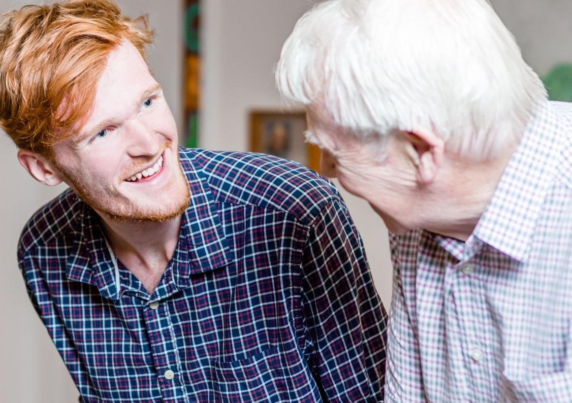 A young man talking to an elderly man with dementia