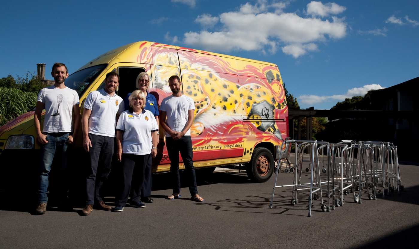 A group of people standing next to a brightly coloured van
