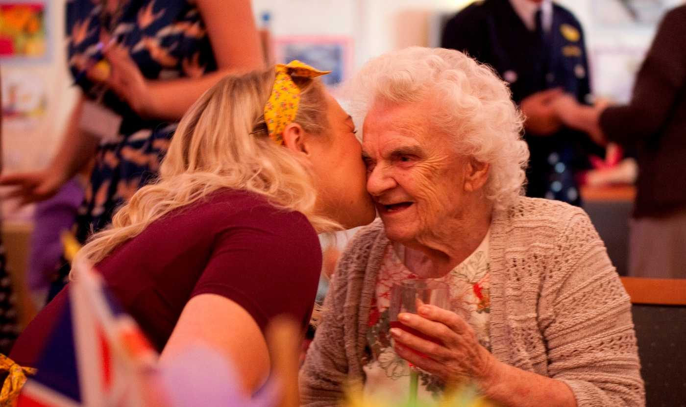 A younger lady kissing an elderly lady on the cheek