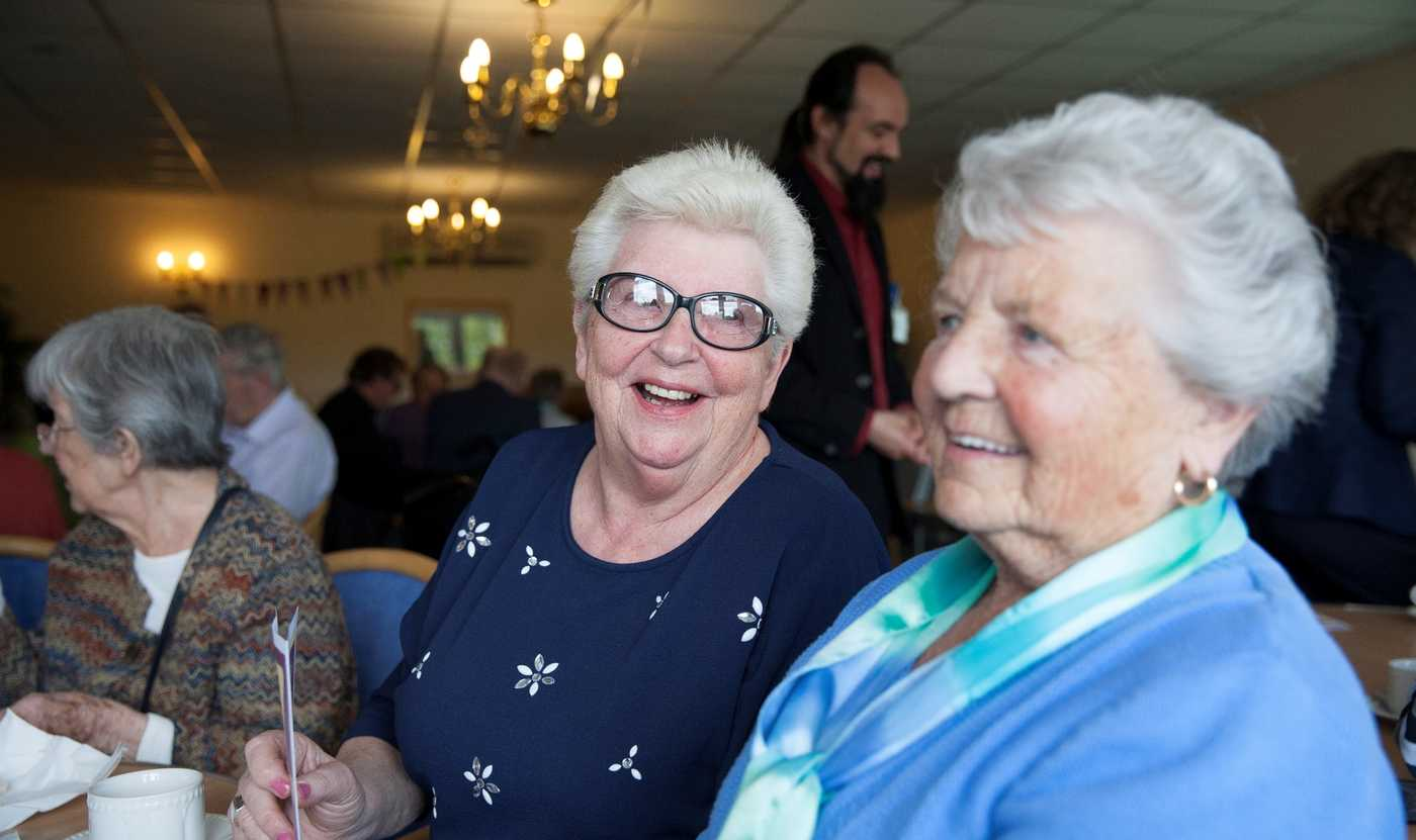Two elderly ladies drinking tea and laughing together