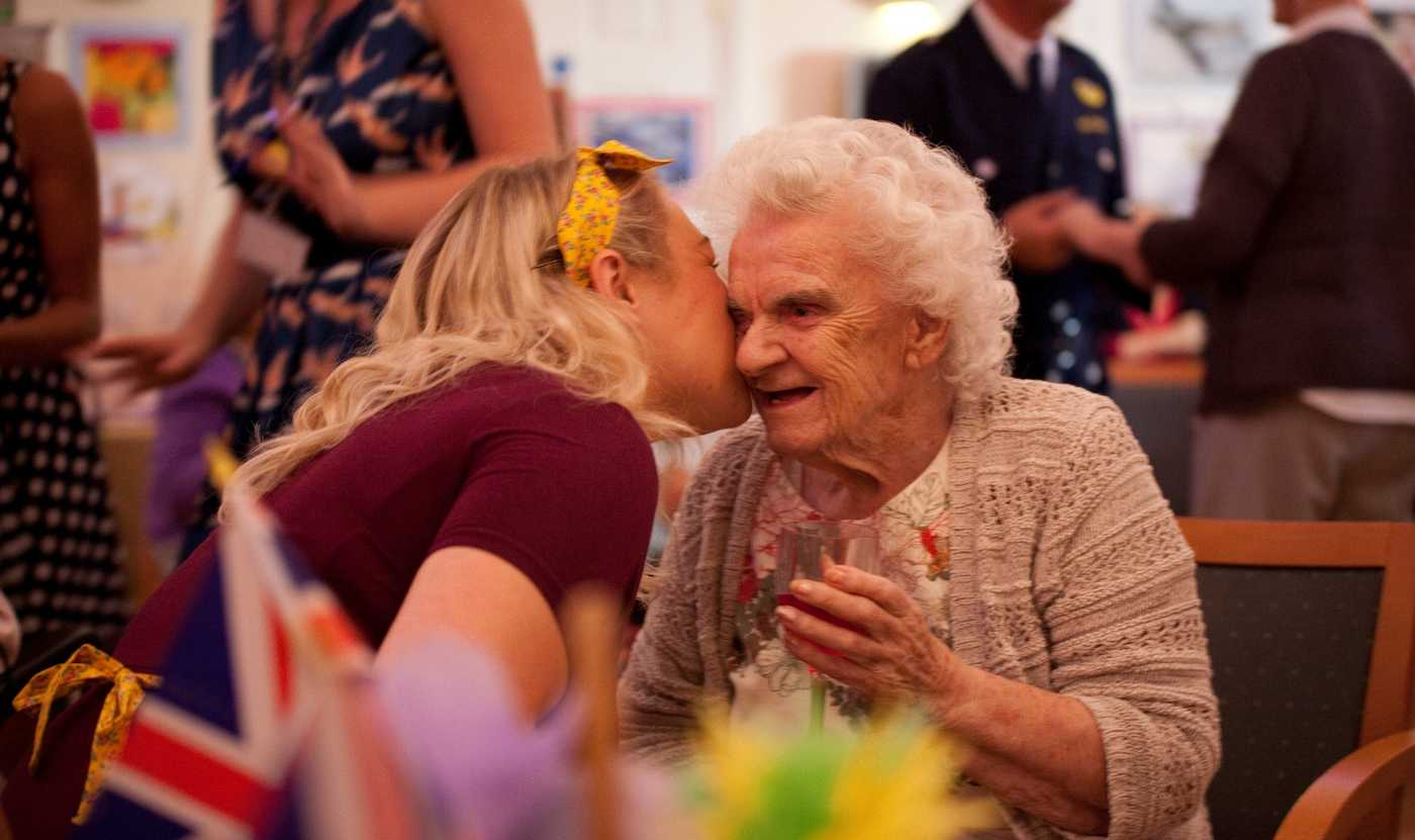 A younger lady kisses an elderly lady on the cheek