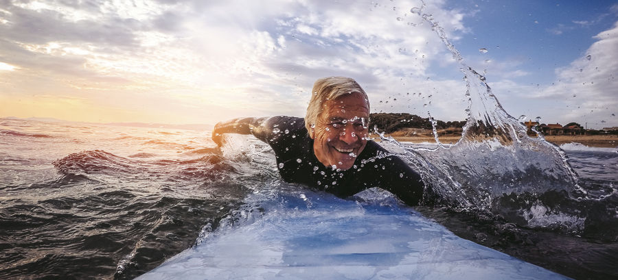 Older surfer demonstrates the value of exercising as an older adult