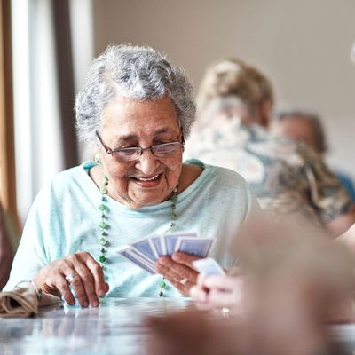 A lady plays card while staying in a care home for respite care in Bristol