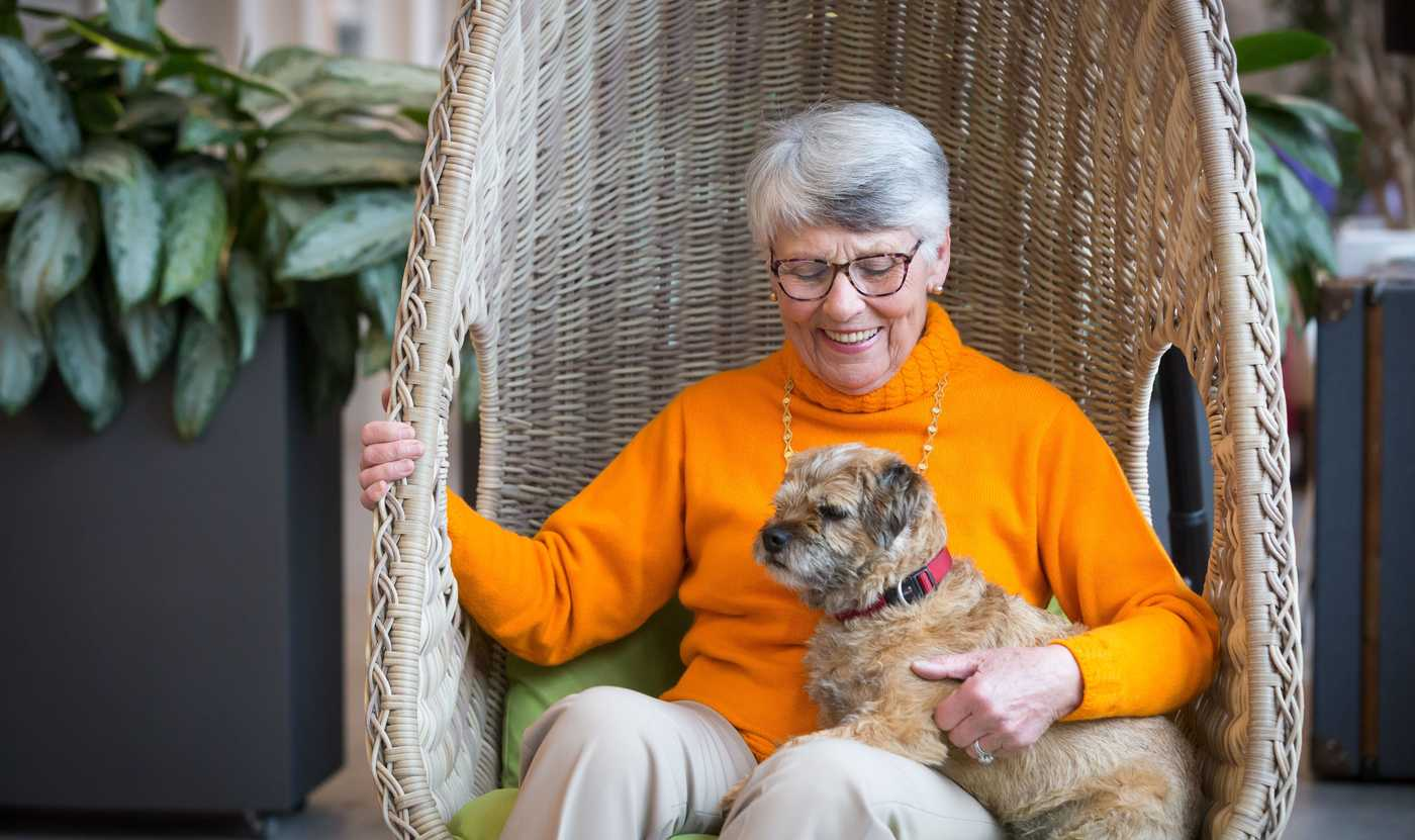 Angela sits with the pet in The Chocolate Quarter, a pet-friendly retirement village in Bristol