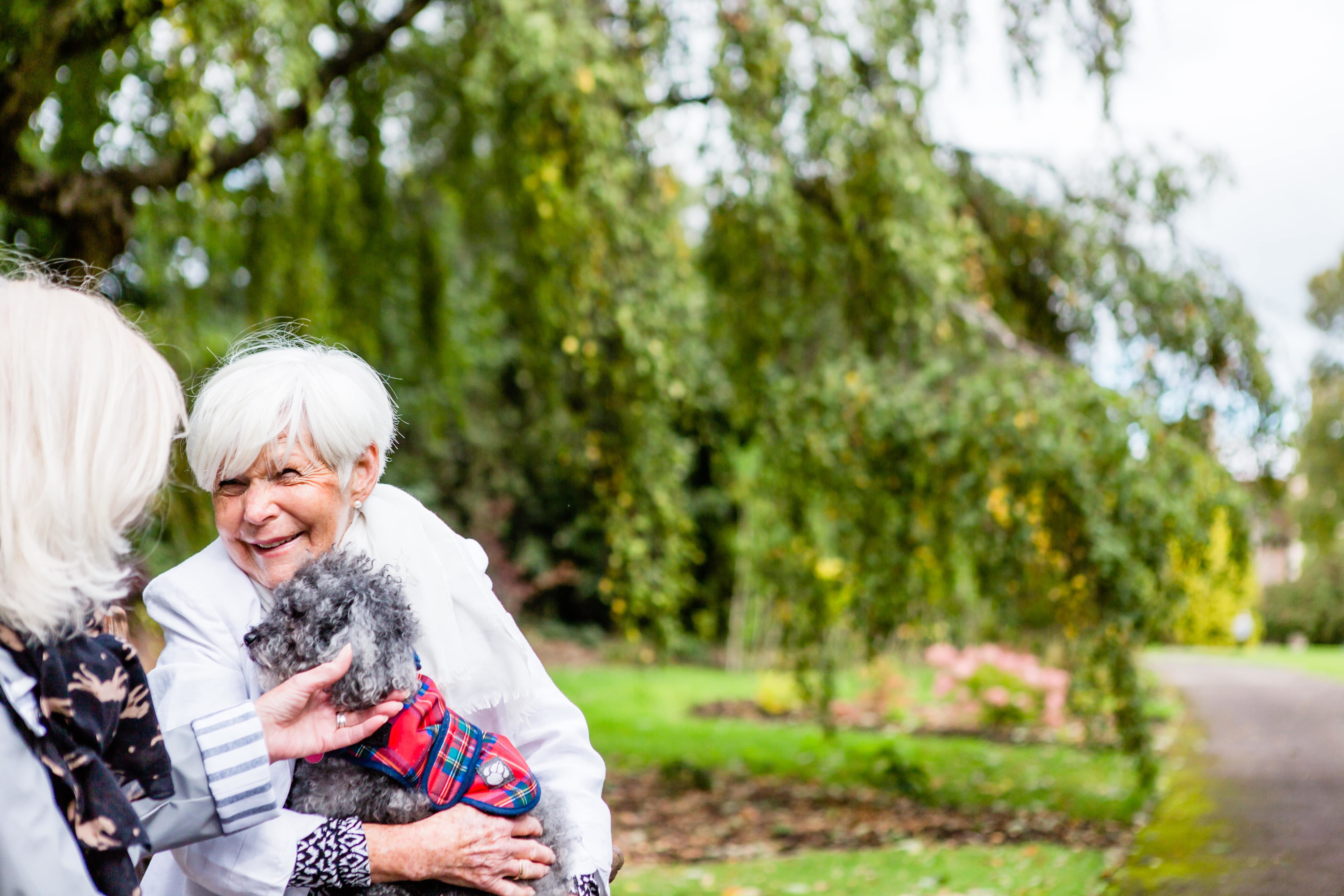 What is a retirement village? Somewhere you can feel at home. Photo of two ladies talking with a dog in the beautiful gardens at Cote Lane, one of our pet friendly retirement villages in Bristol.