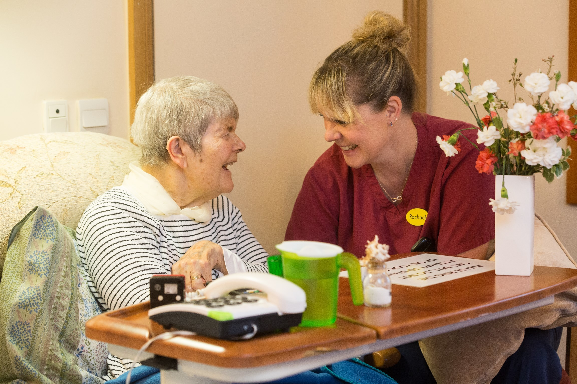 A lady receiving nursing care in Bristol and a nurse smile at each other