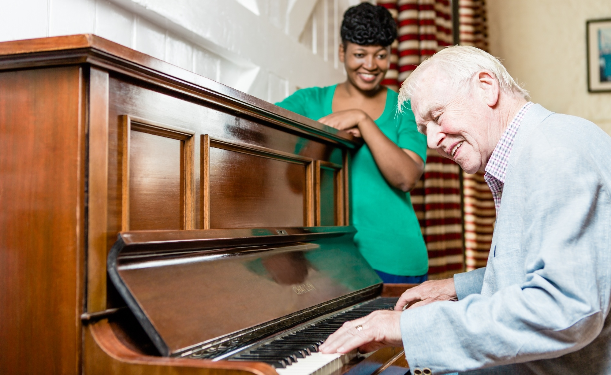 An elderly man playing the piano
