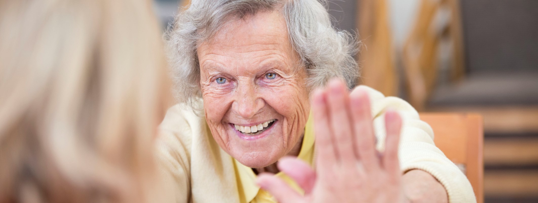 An elderly lady touches hands with a younger lady at her care home in Bristol
