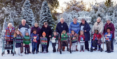 The cast of Old People's Home for 4 Year Olds are wearing Christmas jumpers and stand in front of a snowy backdrop.