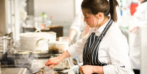 Young female chef is a striped apron prepares food on a stove