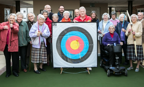 a group of residents pose in front of an archery target