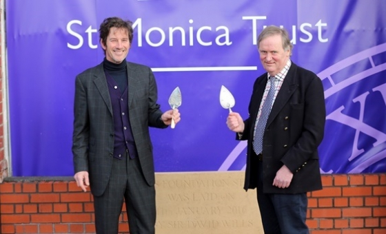 Cosmo Fry and Sir David Wills pose with ceremonial trowels in front of the foundation stone
