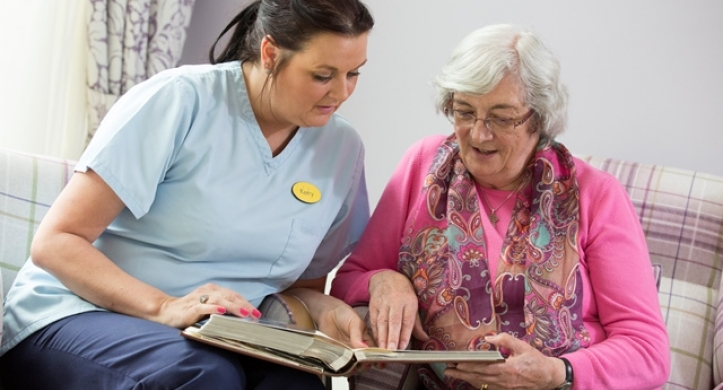 Care and support worker looks at a resident's photo album