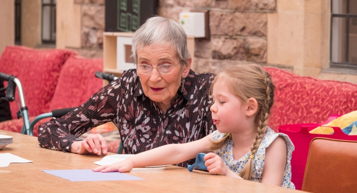 Sheila and Eva sit at a table drawing a picture together